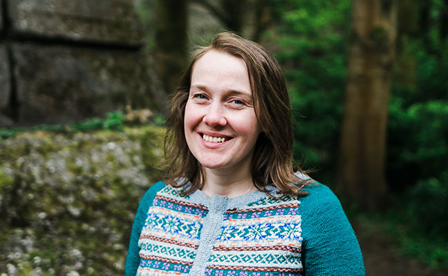 white woman in mid-30s with mid-length light brown hair, wearing a patterned knit cardigan, with trees in the background